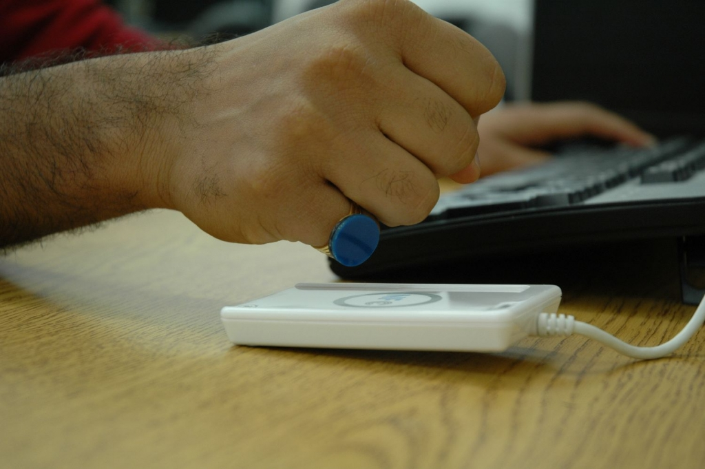 A user holding their ring containing a small NFC tag up to the NFC reader of a Laptop.